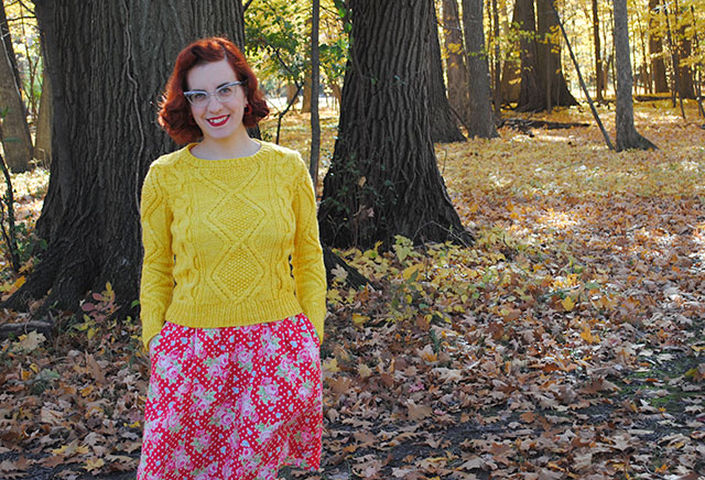 A chunky cabled pullover and fallen leaves